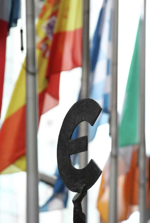 A statue holding the Euro sign is pictured with some flags of EU countries outside the European Parliament building in Brussels, Friday, Oct. 12, 2012. The European Union won the Nobel Peace Prize on Friday for its efforts to promote peace and democracy in Europe, despite being in the midst of its biggest crisis since the bloc was created in the 1950s. (AP Photo/Yves Logghe) Photo: Yves Logghe / AP