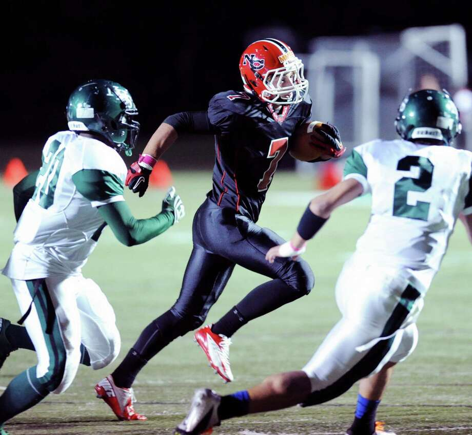 Grady Lynch # 7 of New Canaan runs to the outside while being pursued by Norwalk defenders Andre Cork, left, # 20 and Andy Lovo # 2 during the high School football game between New Canaan High School and Norwalk High School at New Canaan, Friday night, Oct. 12, 2012. Photo: Bob Luckey / Greenwich Time
