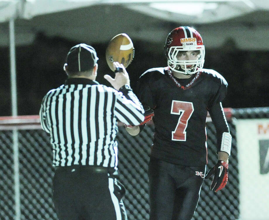 Grady Lynch # 7 of New Canaan hands the ball to the ref after scoring a touchdown during the high School football game between New Canaan High School and Norwalk High School at New Canaan, Friday night, Oct. 12, 2012. Photo: Bob Luckey / Greenwich Time