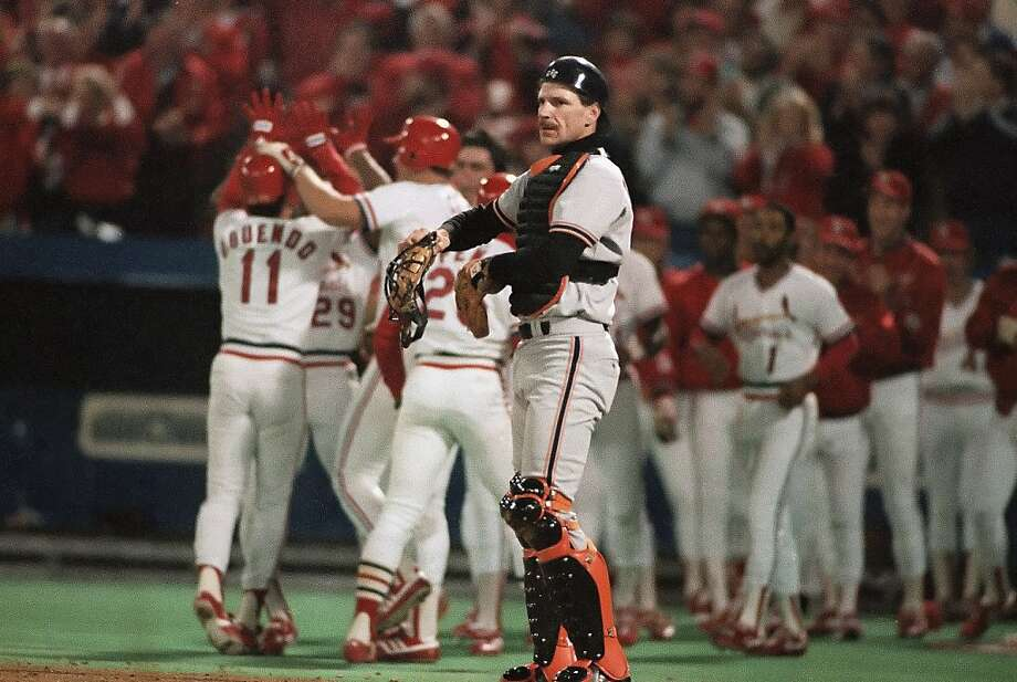Giants catcher Bob Brenly unmasks his disappointment as the Cardinals' Jose Oquendo (11) is mobbed by teammates following his three-run homer in the seventh game of the 1987 NLCS. Photo: John Swart, ASSOCIATED PRESS
