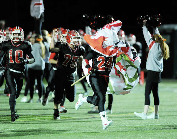 Max Wilson # 24 of New Canaan gets caught up in the banner while entering the field during the start of the High School football game between New Canaan High School and Norwalk High School at New Canaan, Friday night, Oct. 12, 2012. At right is teammate Louis Hagopian # 10. Photo: Bob Luckey / Greenwich Time