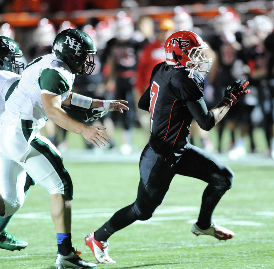 At right, Grady Lynch # 7 of New Canaan runs to the outside during the high School football game between New Canaan High School and Norwalk High School at New Canaan, Friday night, Oct. 12, 2012. Photo: Bob Luckey / Greenwich Time