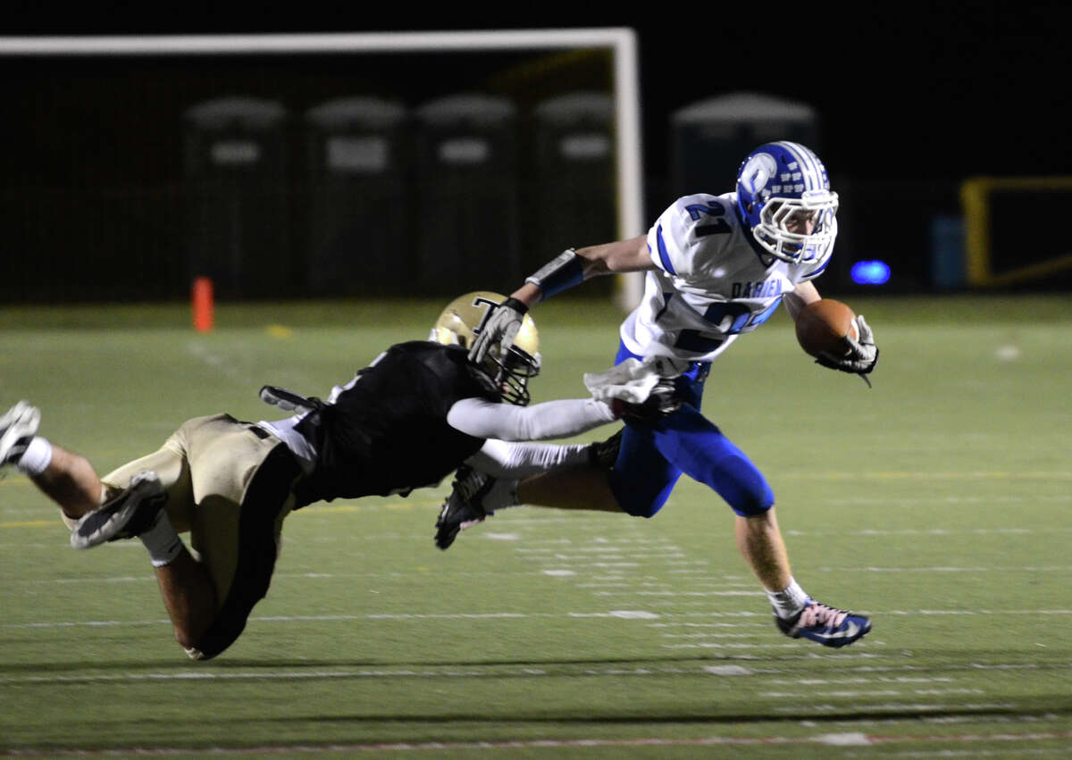 Darien's Nicholas Lombardo (21) carries the ball as Trumbull's Ryan Keklik (5) defends during the football game at Trumbull High School on Friday, Oct. 12, 2012.