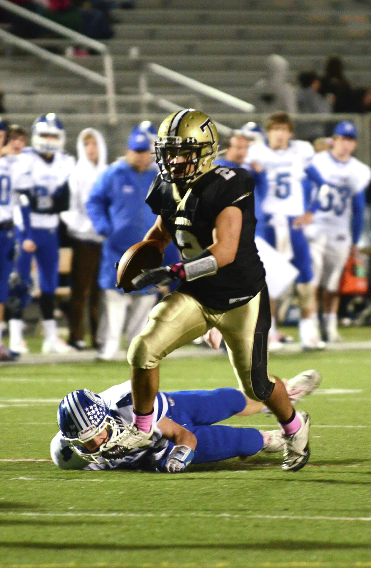 Trumbull's Ryan Pearson (2) carries the ball, stepping over Darien defender Jackson Whiting (4), during the football game against Darien at Trumbull High School on Friday, Oct. 12, 2012.