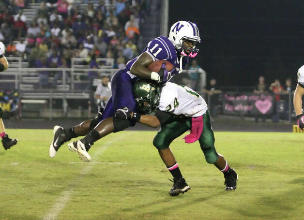 Newton runningback Anthony Hadnot, 11, is tackled by East Chambers' Dominique Marshall during the game Friday at Singletary Stadium in Newton. Matt Billiot/Special to the Enterprise