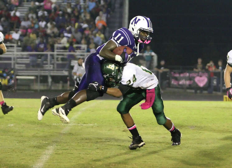 Newton runningback Anthony Hadnot, 11, is tackled by East Chambers' Dominique Marshall during the ga