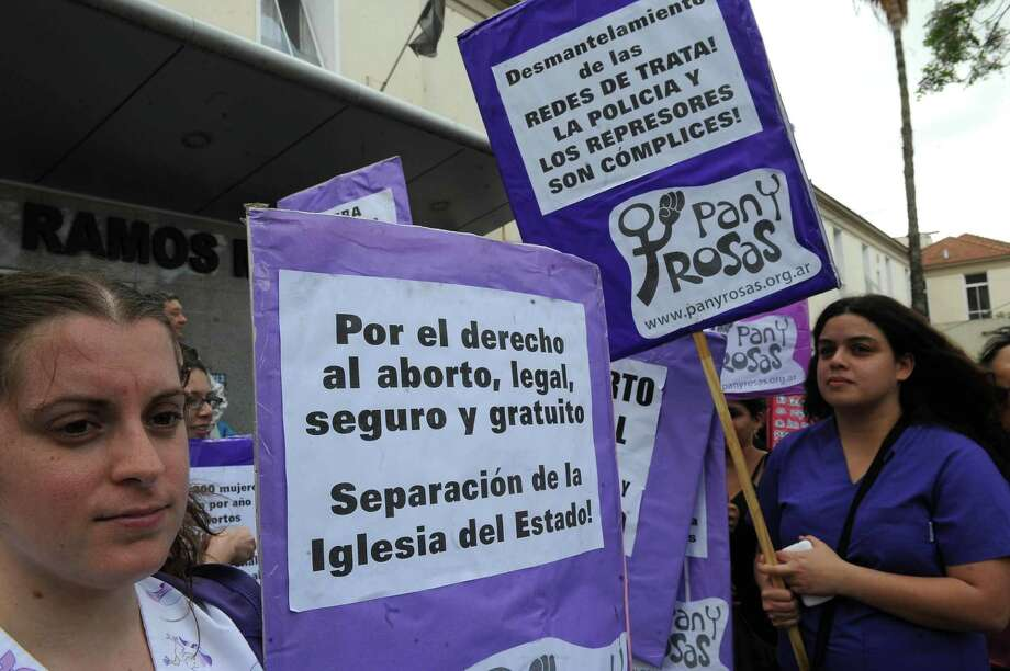 """Demonstrators show their support for a woman who was granted an abortion after being rescued from a prostitution ring. The sign on the left reads, """"For the right to a legal, safe and free abortion."""" Photo: Raul Ferrari / Telam"""