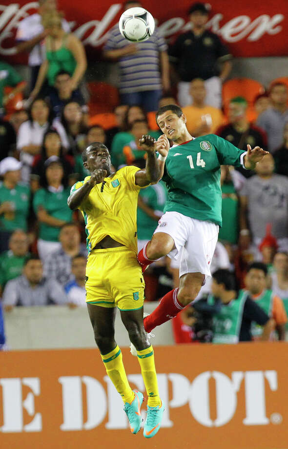 Guyana's Dwain Jacobs, left, battles a header with Mexico's Javier Hernandez, right, during the second half of the FIFA World Cup qualifying match at BBVA Compass Stadium Friday, Oct. 12, 2012, in Houston. Mexico won 5-0. Photo: Cody Duty, Houston Chronicle / © 2012 Houston Chronicle