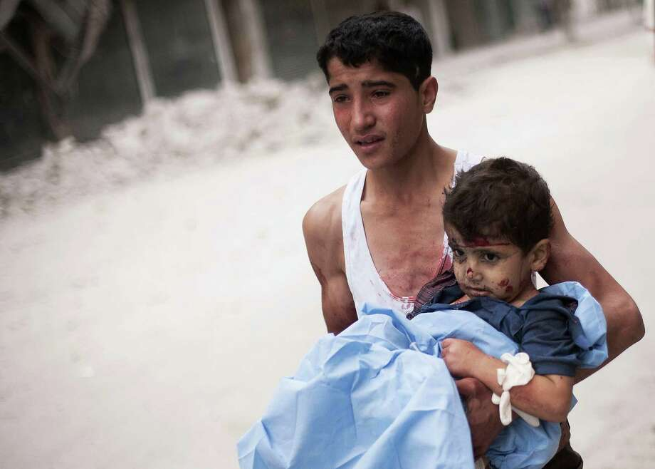 In this Thursday, Oct. 11, 2012 photo, a Syrian youth holds a child wounded by Syrian Army shelling near Dar al-Shifa hospital in Aleppo, Syria. (AP Photo/ Manu Brabo) Photo: Manu Brabo / AP