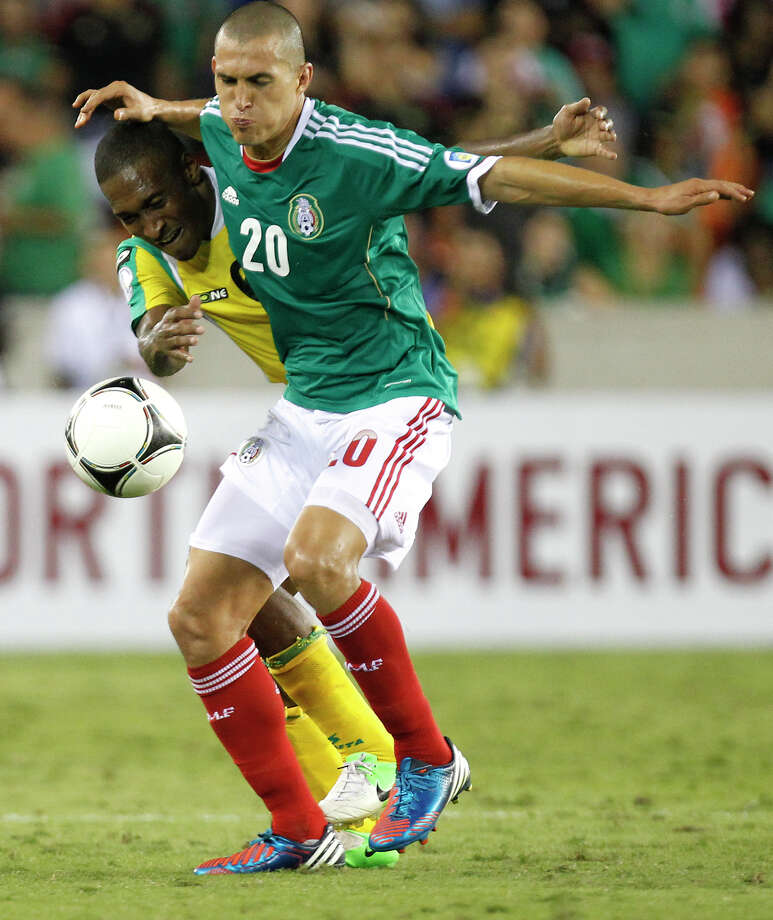 Mexico's Jorge Torres, right, takes possession from Guyana's Ricky Shakes, left, during the second half of their FIFA World Cup qualifying match at BBVA Compass Stadium Friday, Oct. 12, 2012, in Houston. Mexico won 5-0. Photo: Cody Duty, Houston Chronicle / © 2012 Houston Chronicle