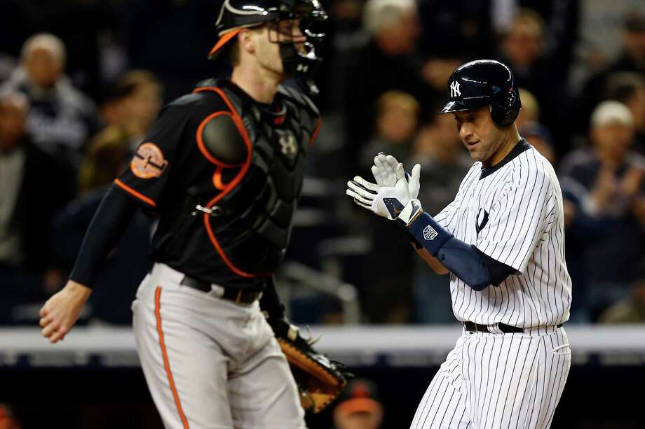 The Yankees' Derek Jeter celebrates while scoring in the sixth inning as Orioles catcher Matt Wieters awaits the relay throw in Game 5 of the AL Division Series. Photo: Elsa / 2012 Getty Images