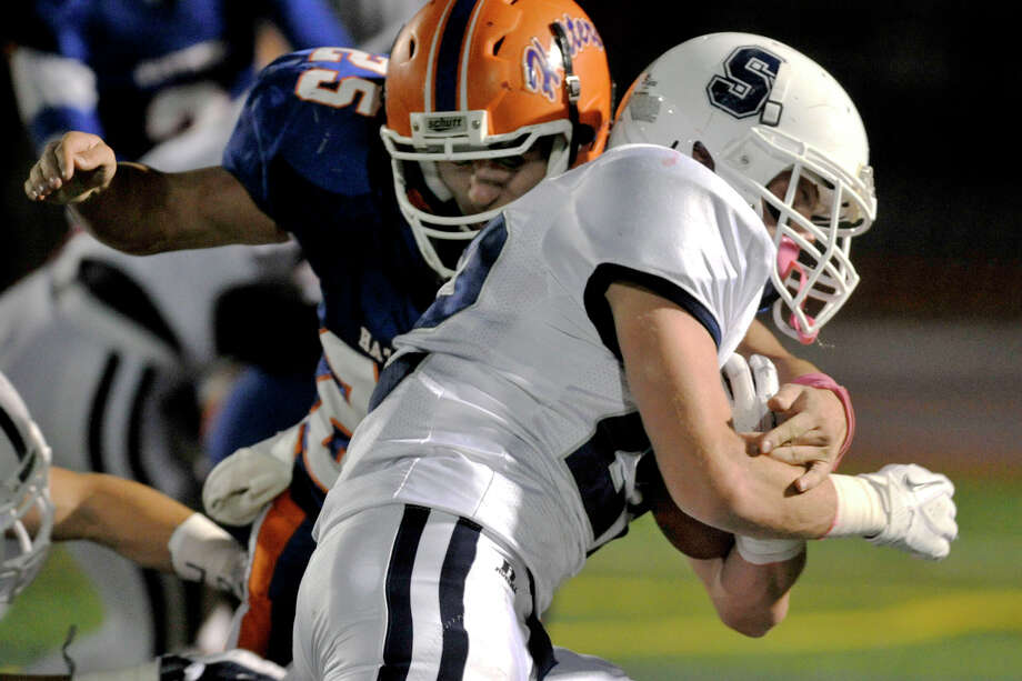 Staples' Joey Zelkowitz runs the ball while under pressure from Danbury's Tyler Harrington during their game at Danbury High School on Friday, Oct. 12, 2012. Photo: Jason Rearick / The News-Times