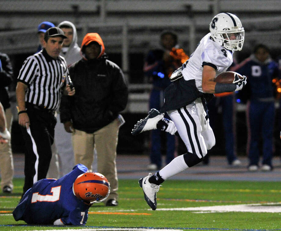 Staples' James Frusciante is tripped up by Danbury's Corey Chaffee during their game at Danbury High School on Friday, Oct. 12, 2012. Photo: Jason Rearick / The News-Times