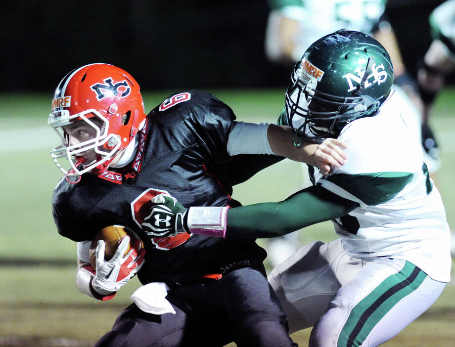 At left, New Canaan quarterback Teddy Bossidy attempts to break free from a Norwalk defensive player during the high School football game between New Canaan High School and Norwalk High School at New Canaan, Friday night, Oct. 12, 2012. Photo: Bob Luckey / Greenwich Time
