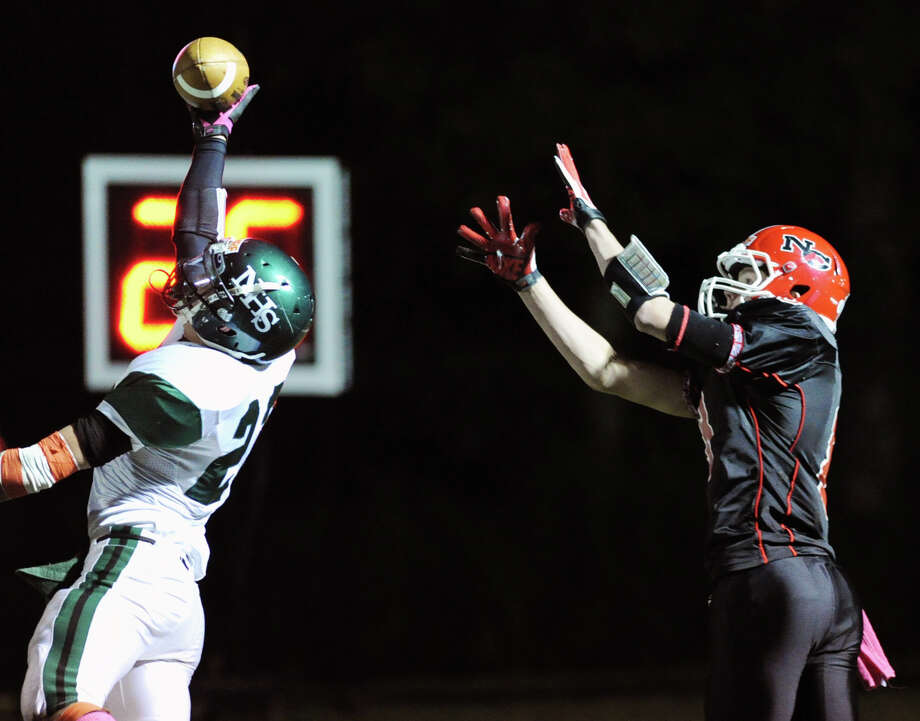 At left, Norwalk's Daniel Jakab # 23 blocks and foils the reception attempt by New Canaan receiver Robby Paul # 8 during the high School football game between New Canaan High School and Norwalk High School at New Canaan, Friday night, Oct. 12, 2012. Photo: Bob Luckey / Greenwich Time