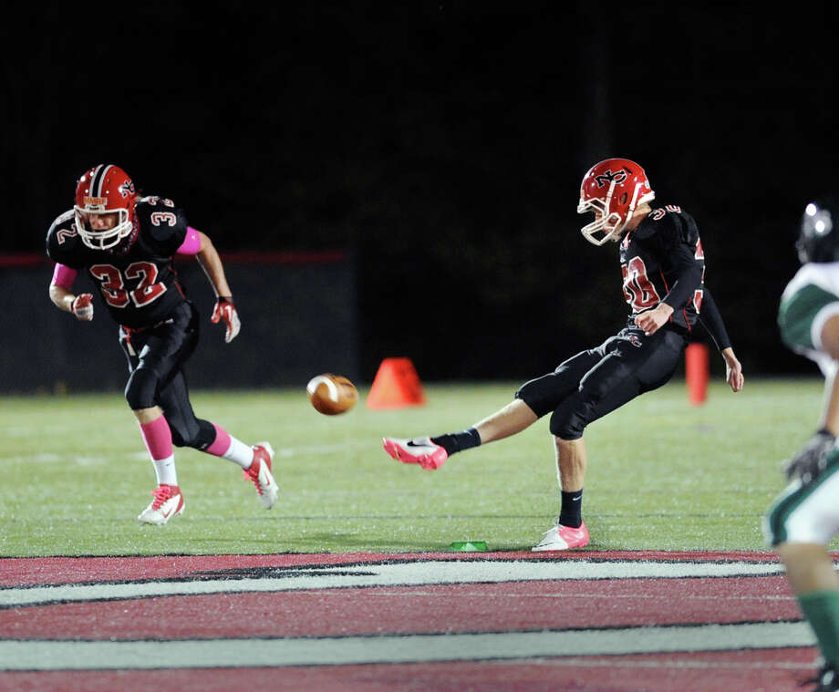 At right, Neal Koller of New Canaan kicks-off as teammate Luke Montgomery # 32 heads downfield during the high School football game between New Canaan High School and Norwalk High School at New Canaan, Friday night, Oct. 12, 2012. Photo: Bob Luckey / Greenwich Time