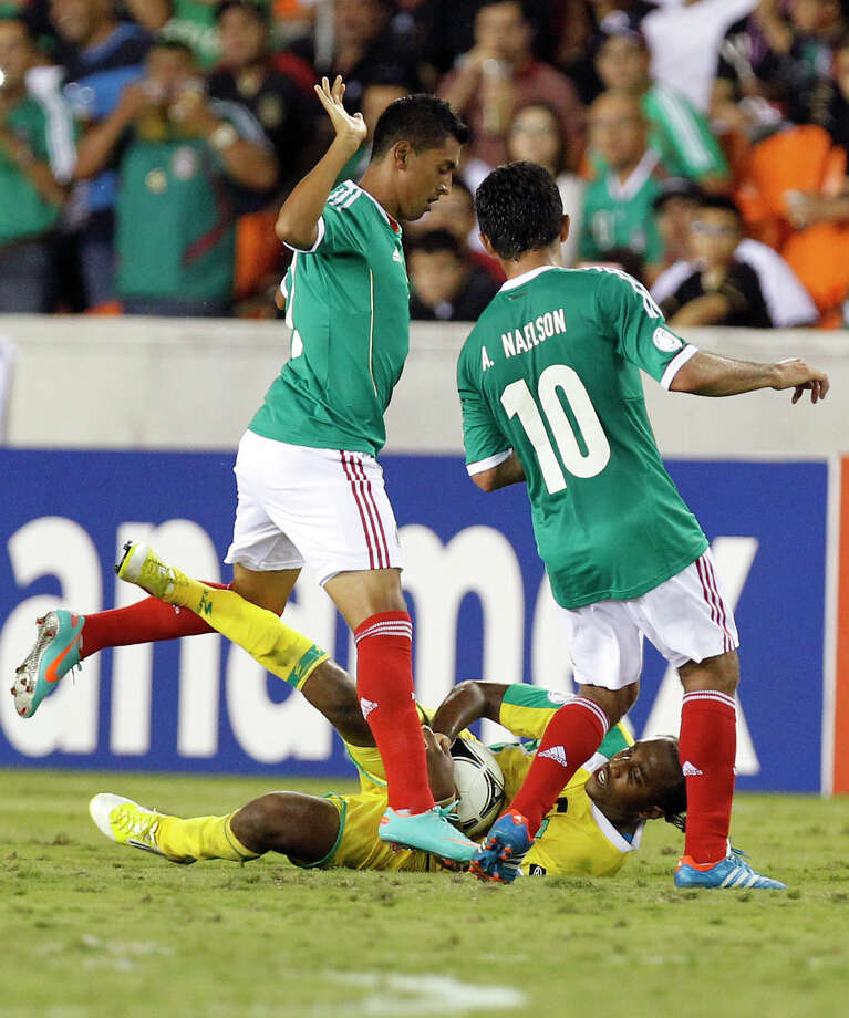 Mexico's Elias Hernandez slows as he and teammate, Antonio Naelson Matias battle Guyana's Walter Moore, center, for possession during the second half. Photo: Cody Duty, Houston Chronicle / © 2012 Houston Chronicle