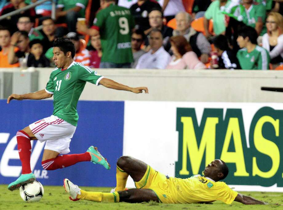 Mexico's Javier Aquino dodges a trip from Guyana's Trayon Beveney. Photo: Cody Duty, Houston Chronicle / © 2012 Houston Chronicle