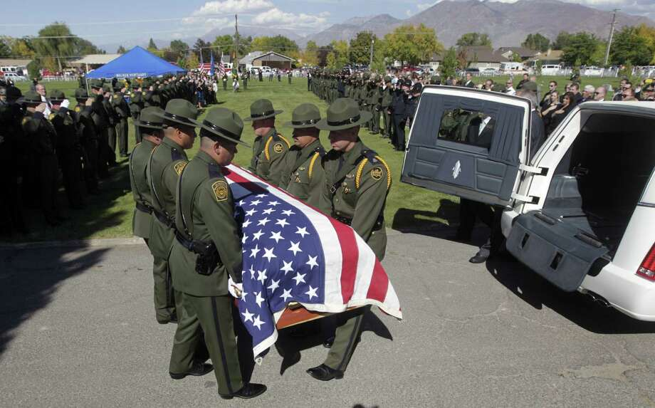 Members of the U.S. Border Patrol carry the casket of U.S. Border Patrol agent Nicholas Ivie during funeral services at the Spanish Fork City Cemetery Thursday, Oct. 11, 2012, in Spanish Fork, Utah. Hundreds turned out for a second funeral service for Nicholas Ivie at Utah Valley University. (AP Photo/Rick Bowmer) Photo: Rick Bowmer