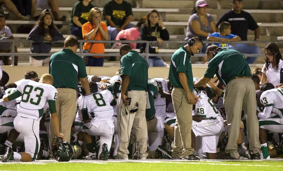 The Cy Falls' team and coaches pray after teammate Leon Nyguen (9) is hit during an onside kick attempt in the fourth quarter of a high school football game at Pridgeon stadium on Friday, Oct. 12, 2012, in Houston. Leon was taken off the field by stretcher. Cy Falls defeated Cy Ridge 38-31 Photo: J. Patric Schneider, For The Chronicle / © 2012 Houston Chronicle
