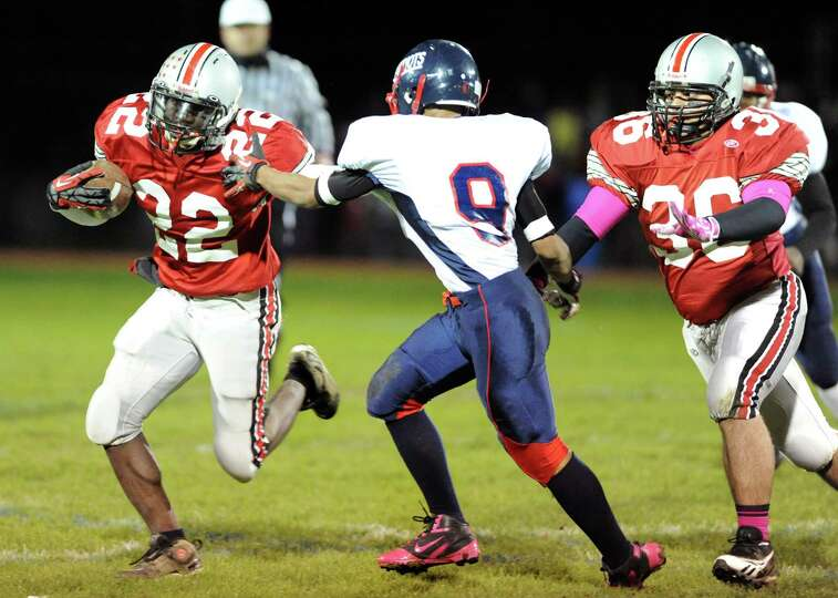 Niskayuna's Troy Garr (22), left, gains yards as Schenectady's Alex Phann (9), center, defends durin
