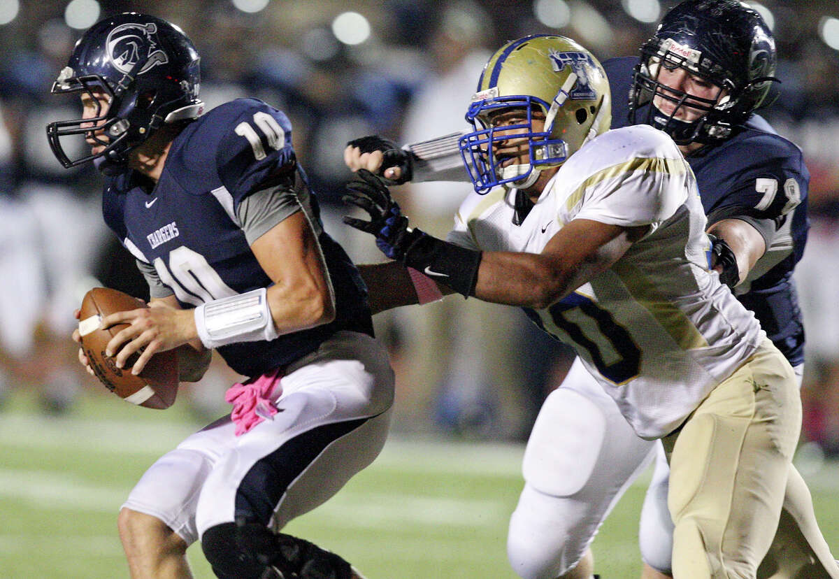 Boerne Champion's Kyle Poeske (left) looks for room around Kerrville Tivy's Jesus Hernandez as Boerne Champion's Ryan Koch moves in on the play during first half action Friday Oct. 12, 2012 at Boerne Independent School District Stadium in Boerne, TX.