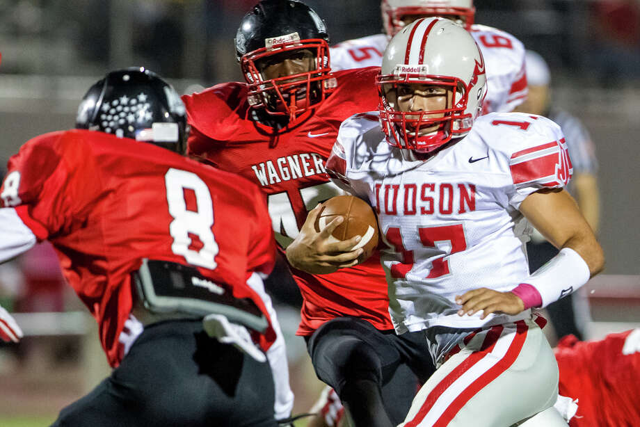 "Judson quarterback Jonathan Gardia (right) looks for room to run as Wagner's Chiante Rome (left) and Duron Smith close in during the first quarter of their game at Rutledge Stadium on Oct. 12, 2012.  Judson won the ""Hammer Bowl"" 30-0.  MARVIN PFEIFFER/ mpfeiffer@express-news.net Photo: MARVIN PFEIFFER, Express-News / Express-News 2012"
