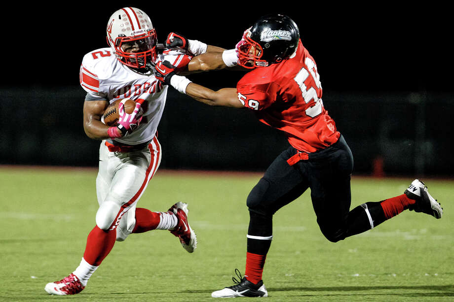 "Judson running back Jarveon Williams (left) tries to elude a tackle by Wagner's Adeo Davis during the second quarter of their game at Rutledge Stadium on Oct. 12, 2012.  Judson won the ""Hammer Bowl"" 30-0.  MARVIN PFEIFFER/ mpfeiffer@express-news.net Photo: MARVIN PFEIFFER, Express-News / Express-News 2012"