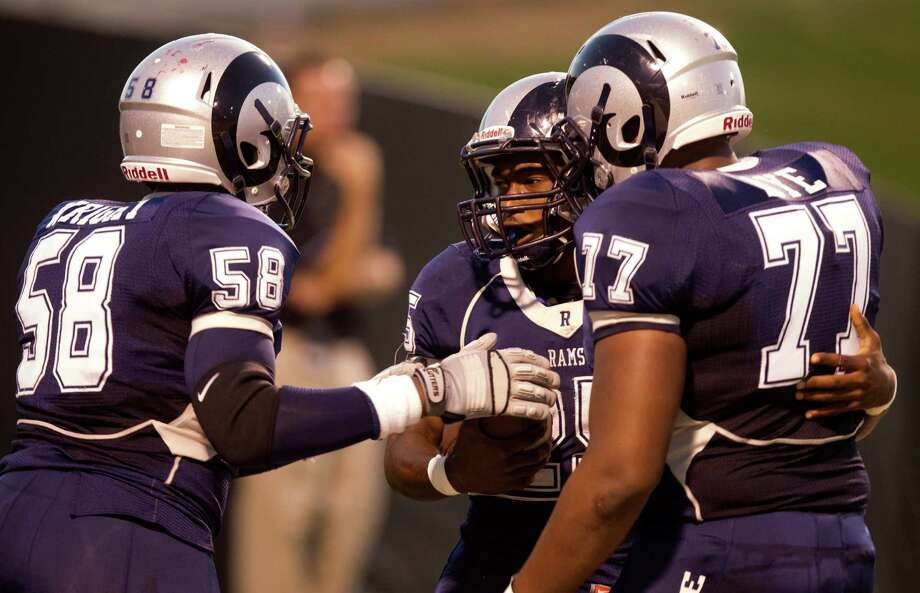 Cy Ridge running back Rennie Childs (25) is congratulated by teammates Willie Wright (58) and Chris Aye (77) after scoring a touchdown during the first quarter of a high school football game at Pridgeon stadium on Friday, Oct. 12, 2012, in Houston. Photo: J. Patric Schneider, For The Chronicle / © 2012 Houston Chronicle