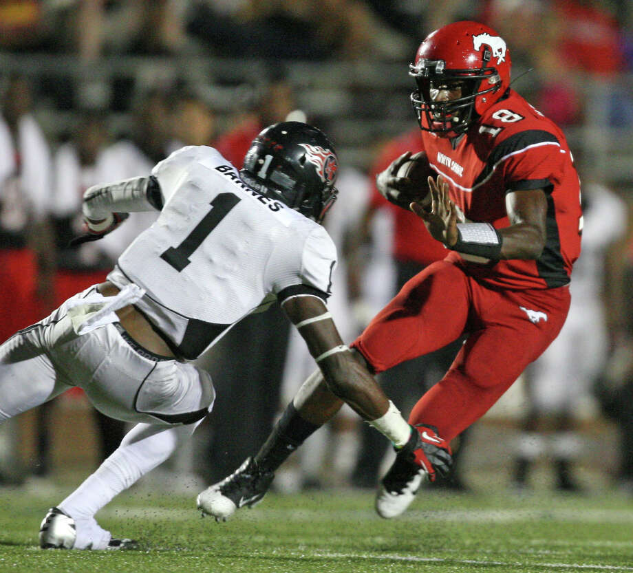 North Shore quarterback Micah Thomas looks for running room as Port Arthur Memorial's Jalen Barnes tries to move in for the tackle Friday night at Galena Park ISD Stadium. Thomas carried 23 times for 153 yards and two touchdowns. Photo: Eric Christian Smith