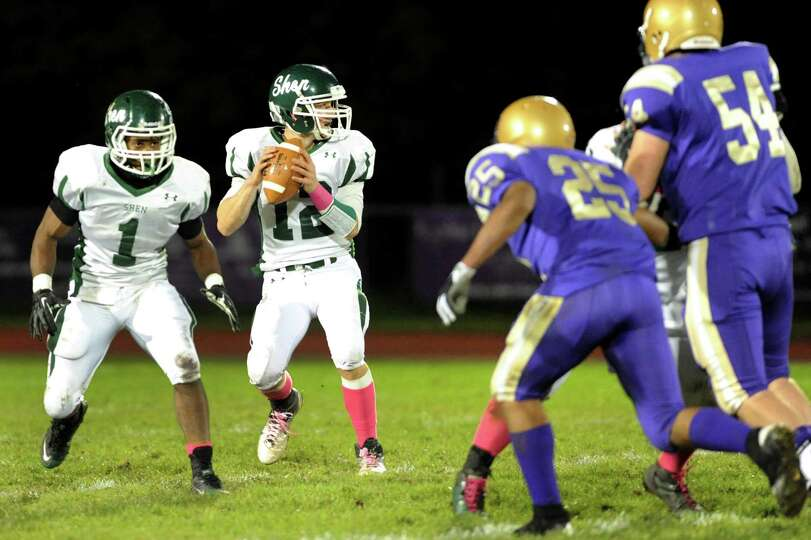 Shenendehowa's quarterback Ryan Buss (12), center, looks to pass during their football game against