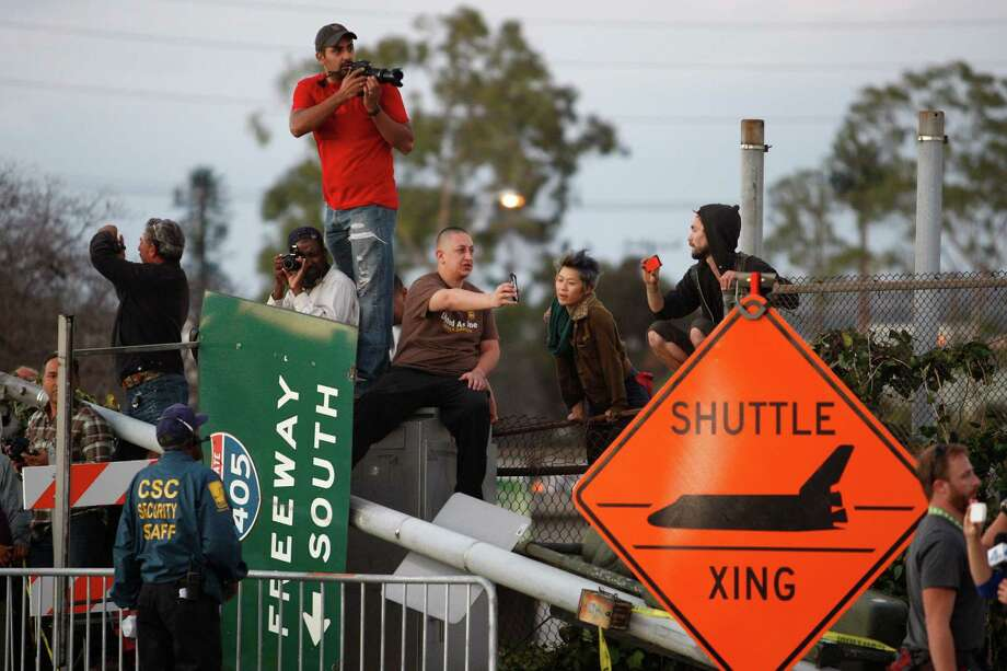 People gather near a shuttle crossing sign and a freeway sign that was taken down to make room as the space shuttle Endeavour is transported to the California Science Center in Exposition Park from Los Angeles International Airport (LAX) on October 12, 2012 in Los Angeles, California. Endeavour was flown cross-country atop NASA's Shuttle Carrier Aircraft from Kennedy Space Center in Florida to LAX on its last flight ever on September 21. From there, it was transported to the California Science Center in Exposition Park where it will be on permanent public display. Completed in 1991, Endeavour was built to replace the space shuttle Challenger which disintegrated during a catastrophic re-entry accident. This fifth and final space shuttle orbiter circled the earth 4,671 times and traveled nearly 123 million miles during its 25 missions from 1992 to 2011. Photo: David McNew, Getty Images / 2012 Getty Images