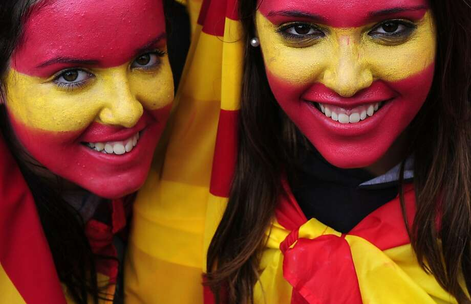 Two girls with their faces painted with the colours of the Spanish flag pose to photographers during the holiday known as Dia de la Hispanidad, Spain's National Day in Barcelona, Spain, Friday, Oct. 12, 2012.  Spain is in recession and under pressure to fix its finances while celebrating the day Christopher Columbus discovered America in the name of the Spanish Crown. (AP Photo/Manu Fernandez) Photo: Manu Fernandez, Associated Press
