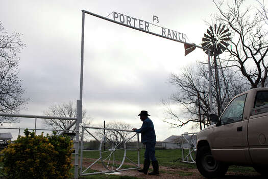 Bernard Porter opens a gate to feed his herd of cattle behind his home early on a Monday morning in Pelham on March 13, 2012. Photo: Lisa Krantz, San Antonio Express-News / © 2012 San Antonio Express-News