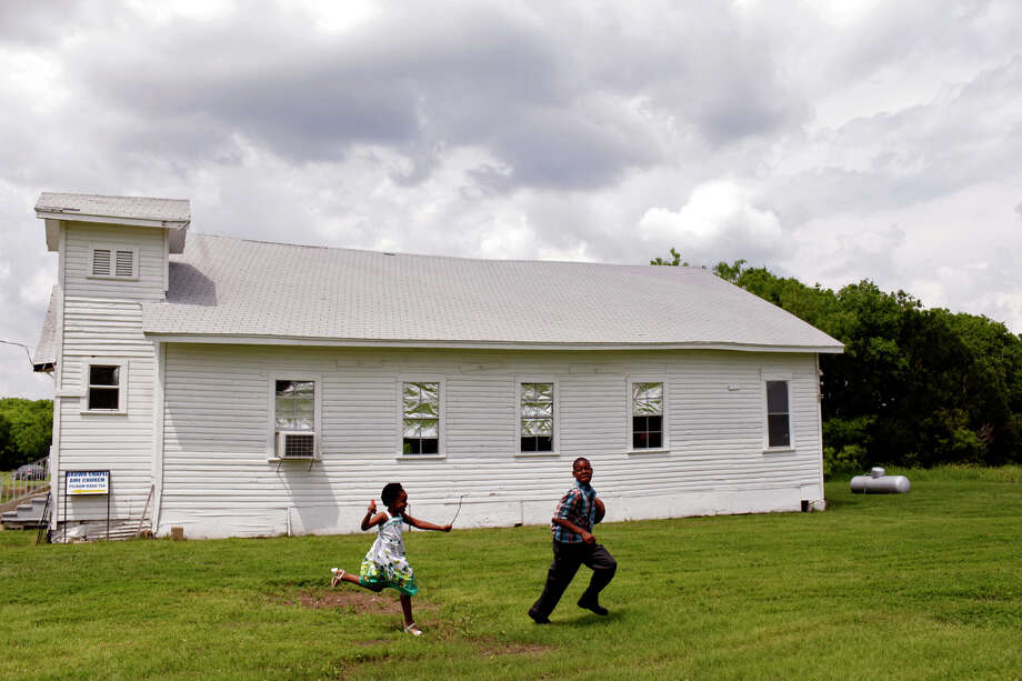 Zaniah Kea, 6, plays with his brother, Jo'vaune Kea, 12, play outside the church their father, Tony Kea, of Killeen, came to lead the service with his mother, Pastor Rosa Kea, for the Easter service at Brown Chapel A.M.E Church in Pelham. Photo: Lisa Krantz, San Antonio Express-News / © 2012 San Antonio Express-News