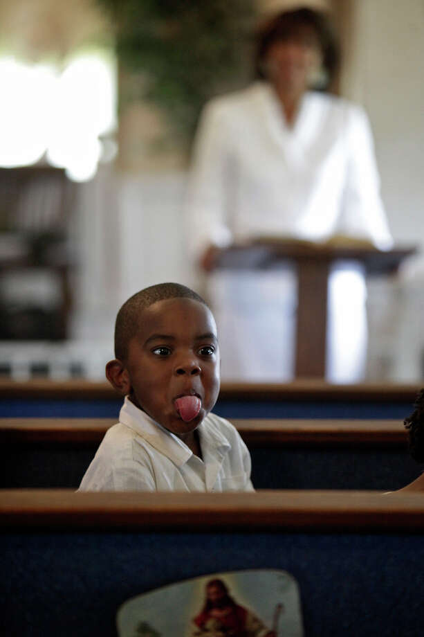 Micah Kea, 3, the son of pastor Tony Kea, of Killeen, Pelham, sticks his tongue out at his friends while Yvonne McNeil-Weaver, a descendant of the Cook family, speaks during the Easter service at Brown Chapel A.M.E Church in Pelham. McNeil-Weaver moved back to Pelham and her family's land three years ago and plans to build a new home there. Photo: Lisa Krantz, San Antonio Express-News / © 2012 San Antonio Express-News