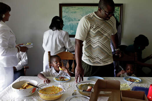 Pastor Tony Kea, of Killeen, has lunch with his family including Micah, 3, left, and Izaiah, 1, at the home of Pelham resident Ted Brackens after the Easter service at Brown Chapel A.M.E Church in Pelham. Photo: Lisa Krantz, San Antonio Express-News / © 2012 San Antonio Express-News