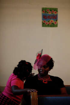 Nyrissia Carter, 6, checks on her mother, Sharmaine Carter, who wasn't feeling well, during the 107th year anniversary celebration of Brown Chapel A.M.E Church, one of two operating churches in Pelham. The Carters are from Killeen where the pastor of the church comes in from for services every week. Photo: Lisa Krantz, San Antonio Express-News / © 2012 San Antonio Express-News