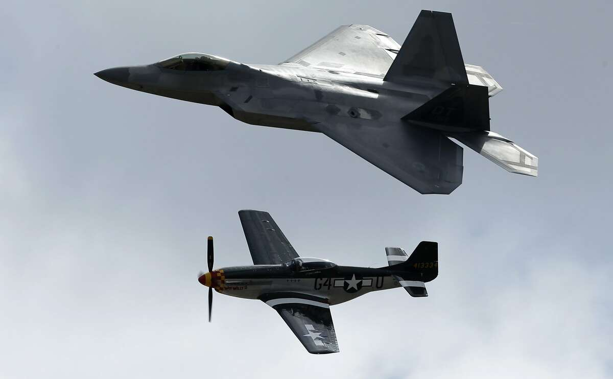 An F-22 Raptor, above, flies with a P-51 Mustang during the Miramar Air Show Friday, Oct. 12, 2012, in San Diego. (AP Photo/Gregory Bull)