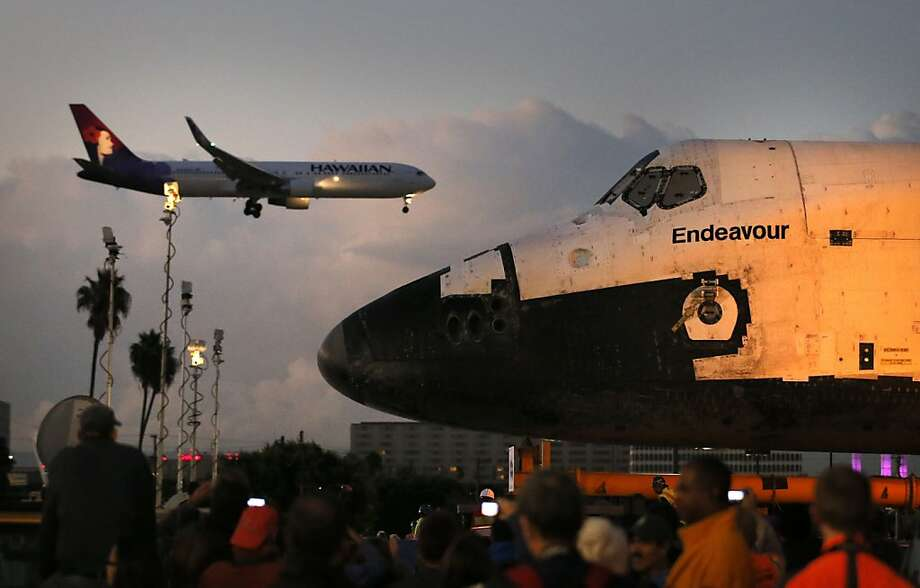 The space shuttle Endeavour sits in a strip mall as a Hawaiian Airlines jet approaches a runway at Los Angeles International Airport in Los Angeles, Friday, Oct. 12, 2012. Endeavour's 12-mile road trip kicked off shortly before midnight Thursday as it moved from its hangar at the airport en route to the California Science Center, its ultimate destination. (AP Photo/Jae C. Hong) Photo: Jae C. Hong, Associated Press
