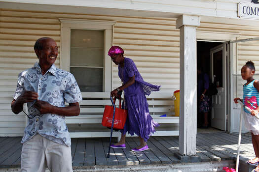 Freddy Carruthers and Darlene Holloway leave the Pelham Community Center as Milan Jones, 8, looks on after an event in Pelham on August 12, 2012. Jones's grandmother, April Van Rader, of Arlington, pastors three churches in the area including Pelham's Wesley United Methodist Church. Photo: Lisa Krantz, San Antonio Express-News / © 2012 San Antonio Express-News