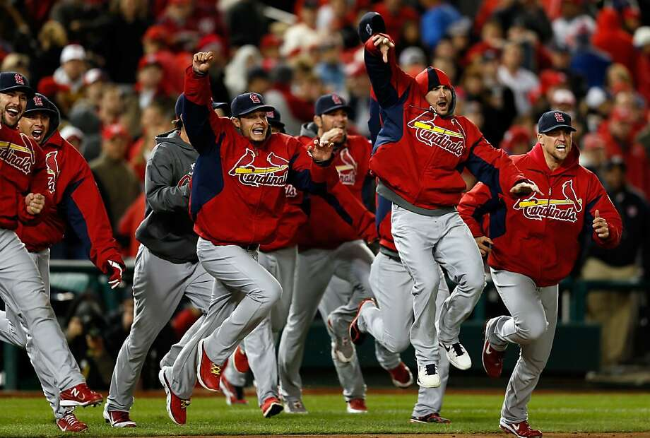 Cardinals players sprint from the dugout to join those on the field after the final out in their series-deciding victory. Photo: Rob Carr, Getty Images