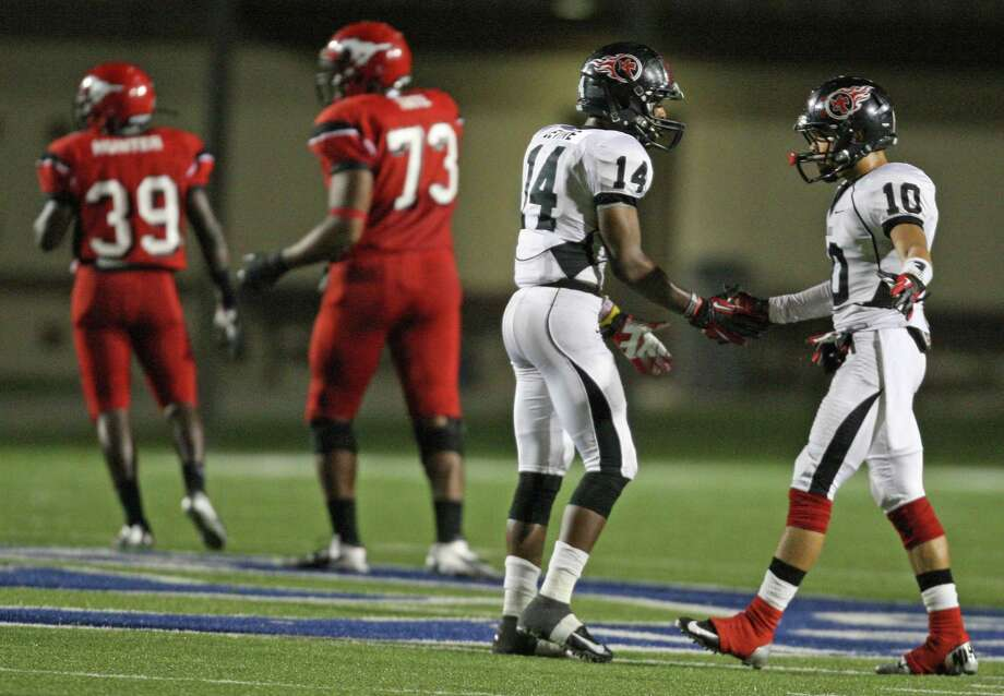 Port Arthur Memorial's CJ Levine (14) and teammate James Jenkins celebrate a Titans defensive stop on third down during the first half of a high school football game against North Shore, Friday, October 12, 2012 at Galena Park ISD Stadium in Houston, TX. Photo: Eric Christian Smith, For The Chronicle