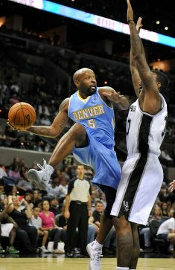 Denver Nuggets guard Anthony Carter looks to pass around San Antonio Spurs forward Josh Powell during the first half of an NBA preseason basketball game on Friday, Oct. 12, 2012, in San Antonio. (Bahram Mark Sobhani / Associated Press)