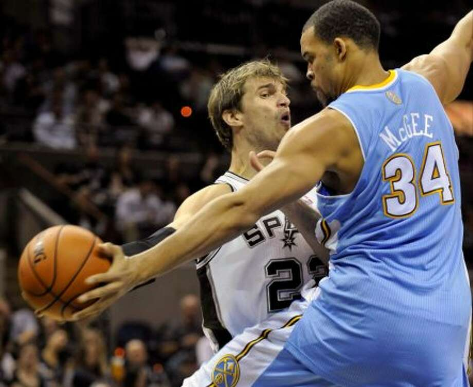 Denver Nuggets center JaVale McGee, right, blocks a pass-attempt by San Antonio Spurs center Tiago Splitter, of Brazil, during the first half of an NBA preseason basketball game on Friday, Oct. 12, 2012, in San Antonio. (Bahram Mark Sobhani / Associated Press)