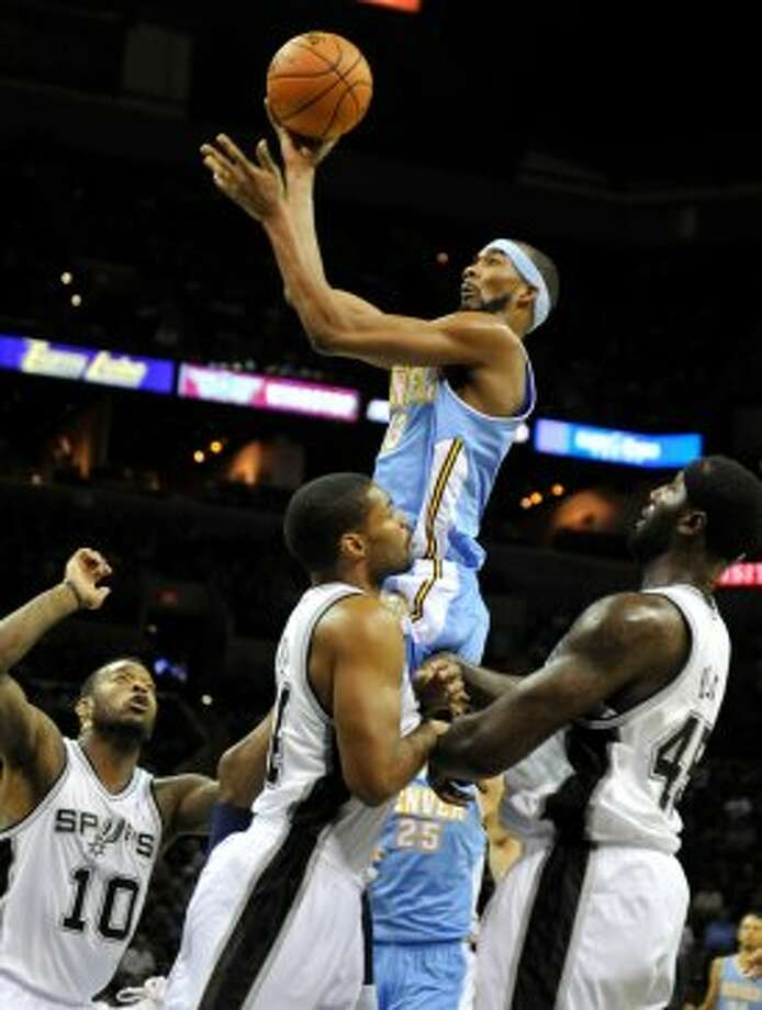 Denver Nuggets forward Corey Brewer, top, shoots over San Antonio Spurs', from left, Josh Powell, Gary Neal and DeJuan Blair during the first half of an NBA preseason basketball game on Friday, Oct. 12, 2012, in San Antonio. (Bahram Mark Sobhani / Associated Press)