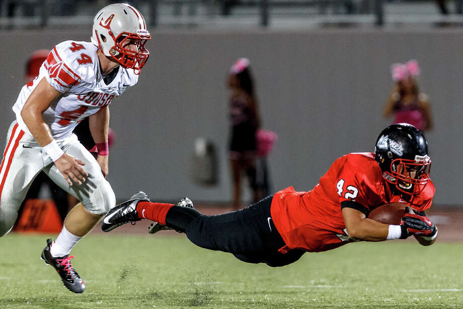 """Wagner's Humberto Hernandez dives for extra yardage with Judson's Colton  Barnes in pursuit during the first quarter of their game at Rutledge Stadium on Oct. 12, 2012.  Judson won the """"Hammer Bowl"""" 30-0.  MARVIN PFEIFFER/ mpfeiffer@express-news.net Photo: MARVIN PFEIFFER, Express-News / Express-News 2012"""