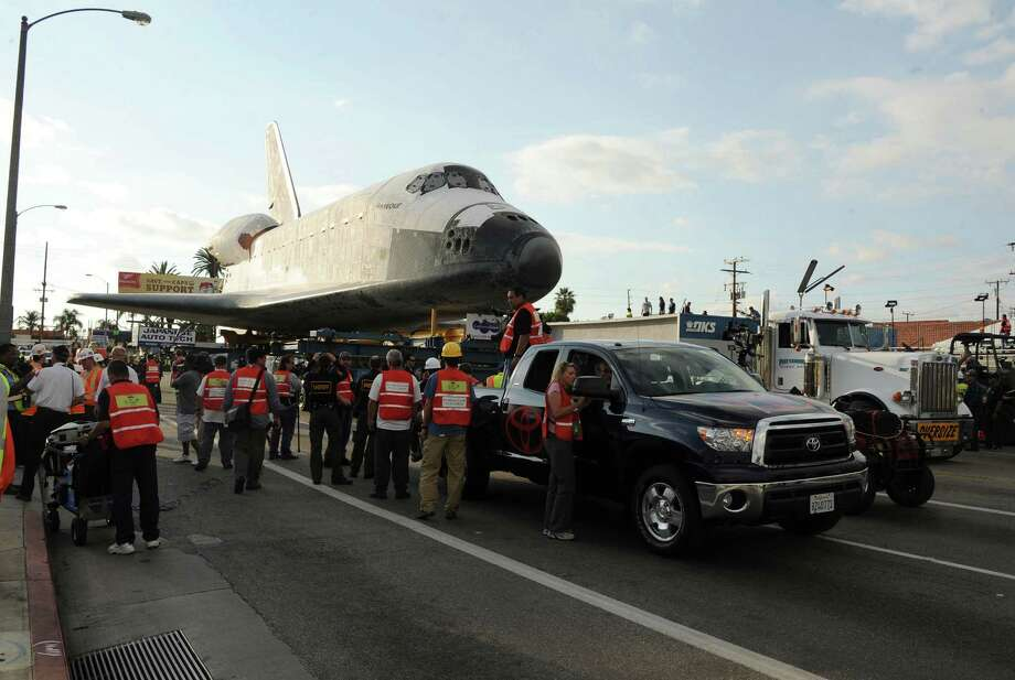 Space shuttle Endeavour travels 12 miles through city streets from Los Angeles International Airport to it's final location at the California Science Center, Friday, October 12, 2012, in Los Angeles, California.  Endeavour flew a total of 25 space missions, with the final one launching in May 2011, and will now serve as a museum showpiece at the California Science Center. (AP Photo/Katy Winn) Photo: Katy Winn, Associated Press / WINNK