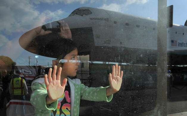 Space Shuttle Endeavour is seen reflected in a window on route from Westchester square to Randy's Donuts during its final ground journey  in  Los Angeles, California on October 12,2012. Over the next two days, the 170,000-pound shuttle will travel at no more than 2 mph along a 12-mile route from LAX to it's final home at the California Science Center. NASA Space Shuttle Program ended in 2011 after 30 years and 135 missions. Photo: Joe Klamar / Associated Press