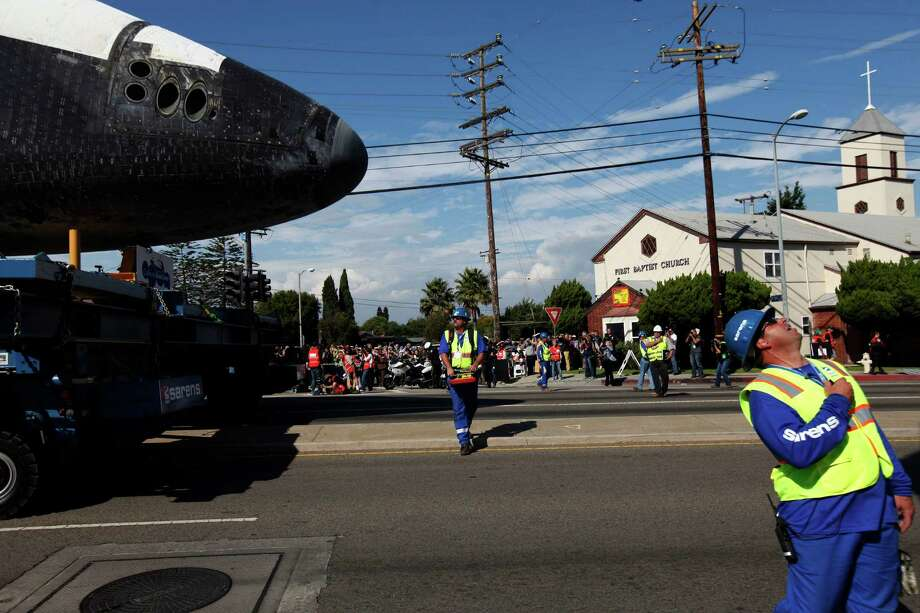 Crews check power lines and other obstructions as the space shuttle Endeavour slowly moves along city streets on a 160-wheel trailer. Photo: Patrick T. Fallon / Associated Press